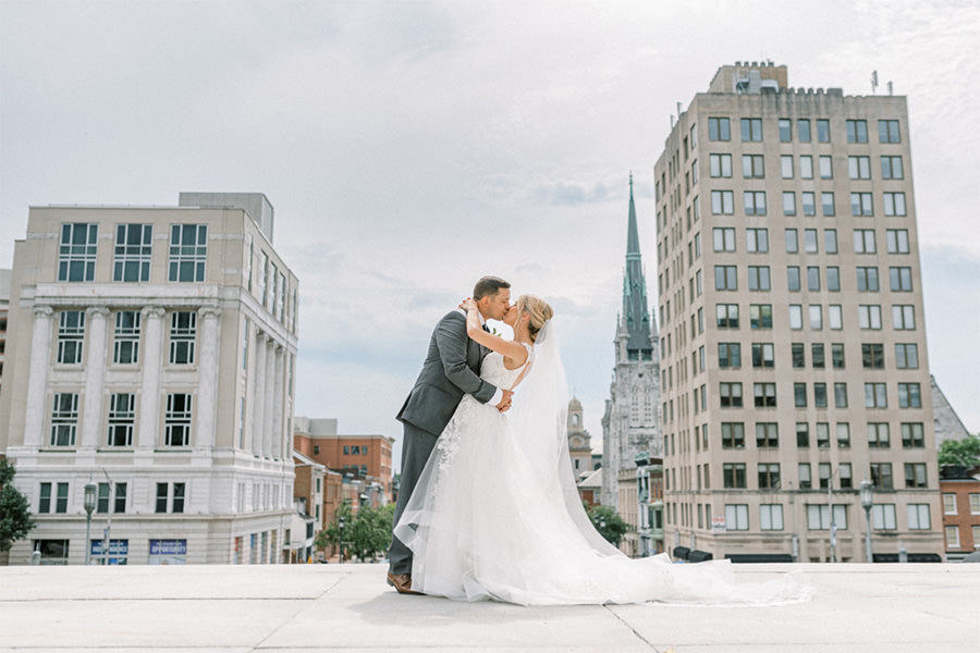 A bride and groom kissing in front of the Harrisburg Capitol building. This is for the article called best wedding photographers in Harrisburg, PA