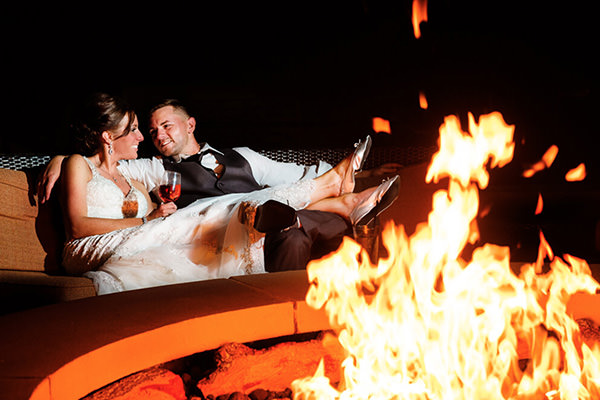 A bride and groom sitting by a fire in Harrisburg, PA