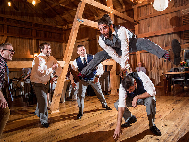 A groomsmen jumping over another guy on the dance floor at a wedding in Reading, PA