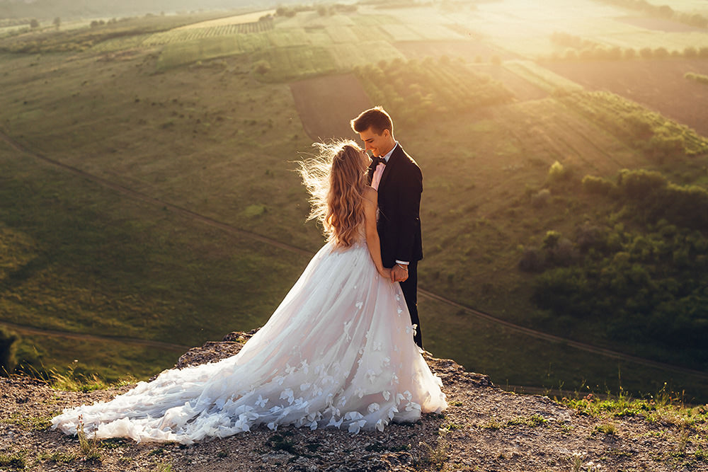 A bride and groom kissing on a mountain at sunset