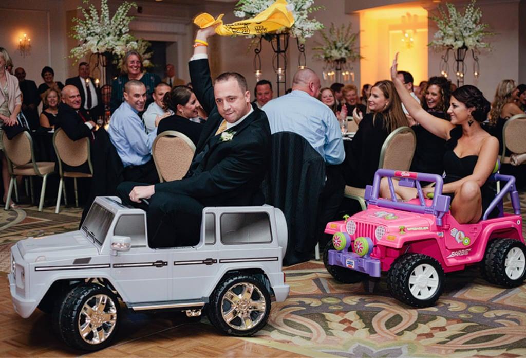 groomsmen and bridesmaid riding into wedding reception on ride on trucks.
