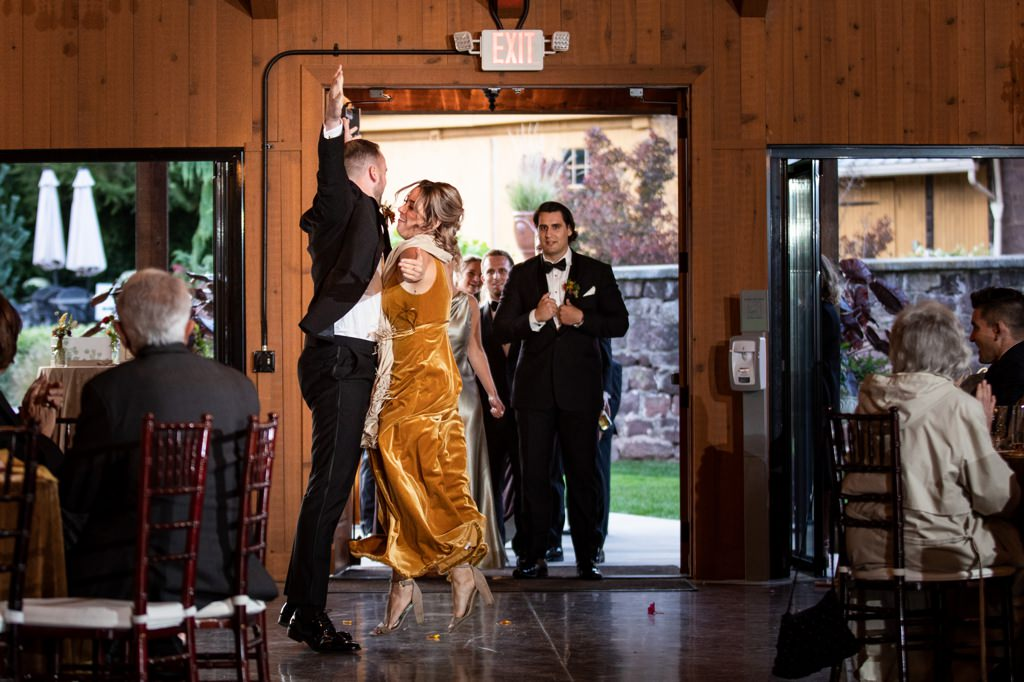 A bridesmaid and groomsmen junling up and giving each other a chest bump