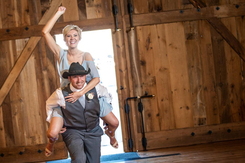 A bridesmaid getting a piggyback ride from the groomsmen during the wedding party entrance at the reception.