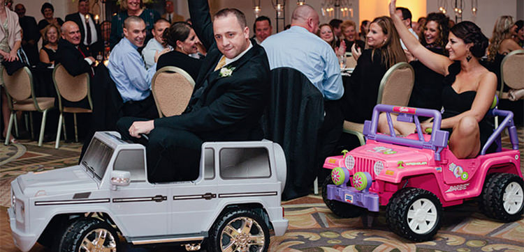 cover photo for the bridal party entrance ideas article. This is a groomsmen and bridesmaid riding into reception on toy cars