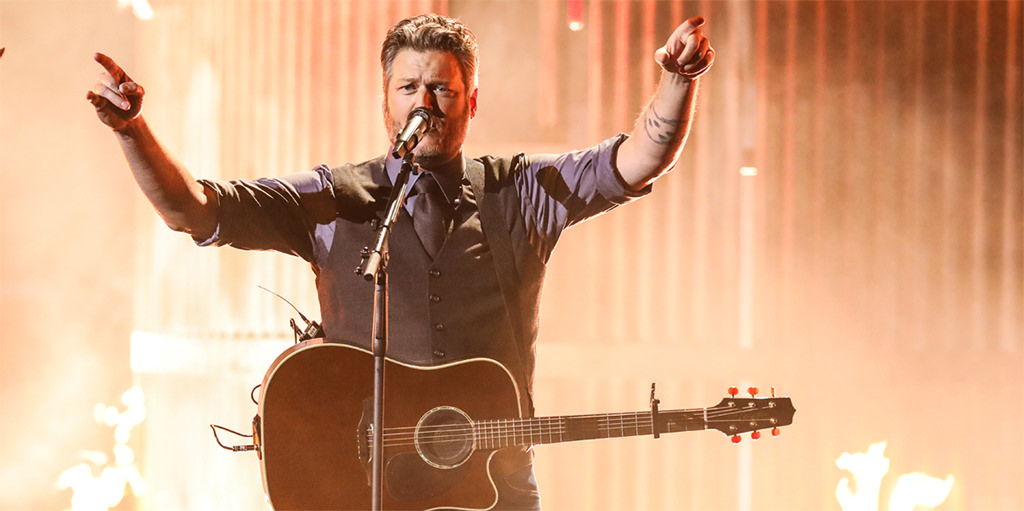 A picture of blake shelton singing a song while holding his guitar. This is for the article called best country songs for wedding.