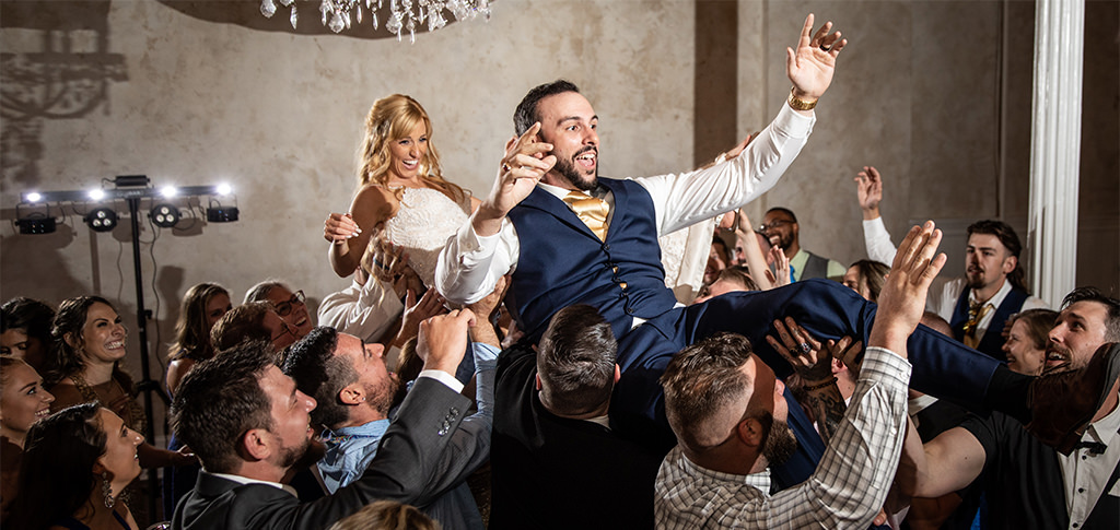 A bride and groom being lifted in the air at their wedding. They were dancing to the best 90s dance songs.