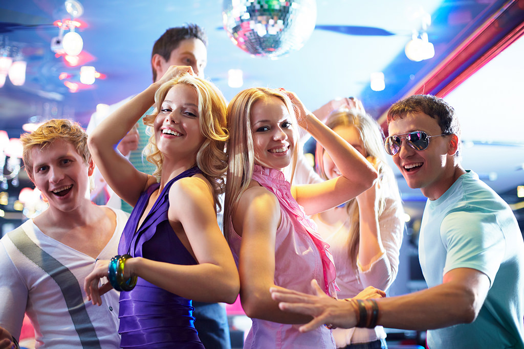 A group of people dancing on the dance floor at a wedding. This is for the article, best 80s wedding dance songs.