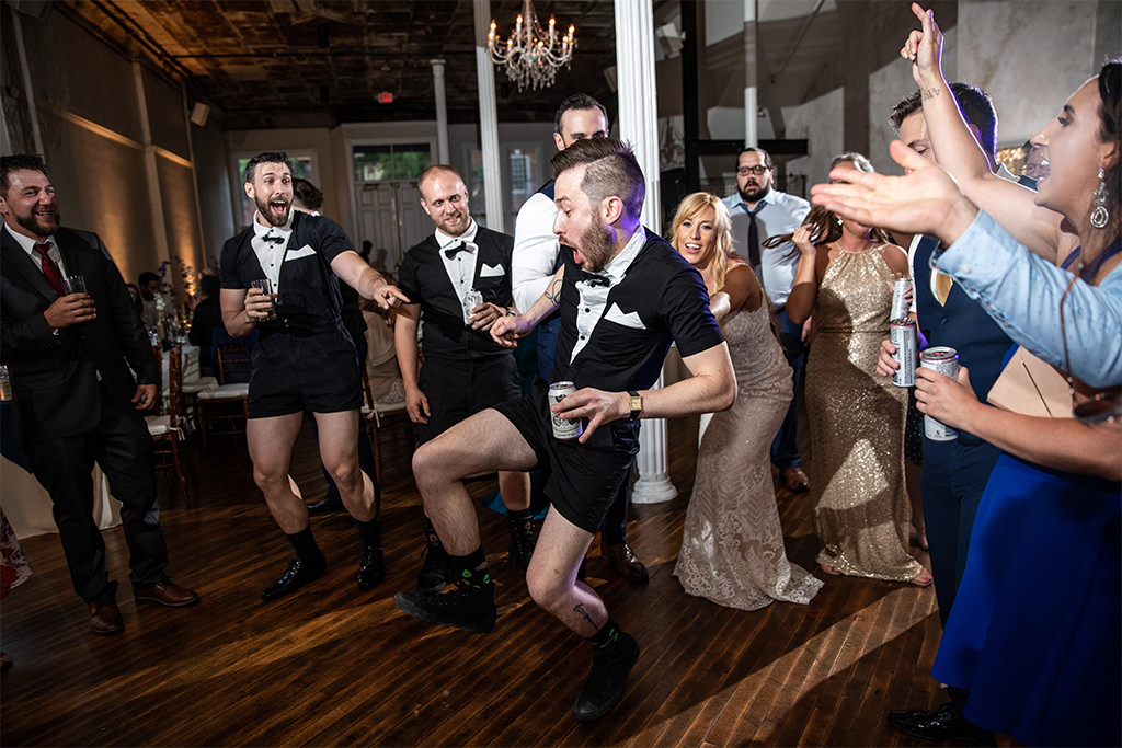 A funny groomsmen dancing in a tuxedo shirt at a wedding