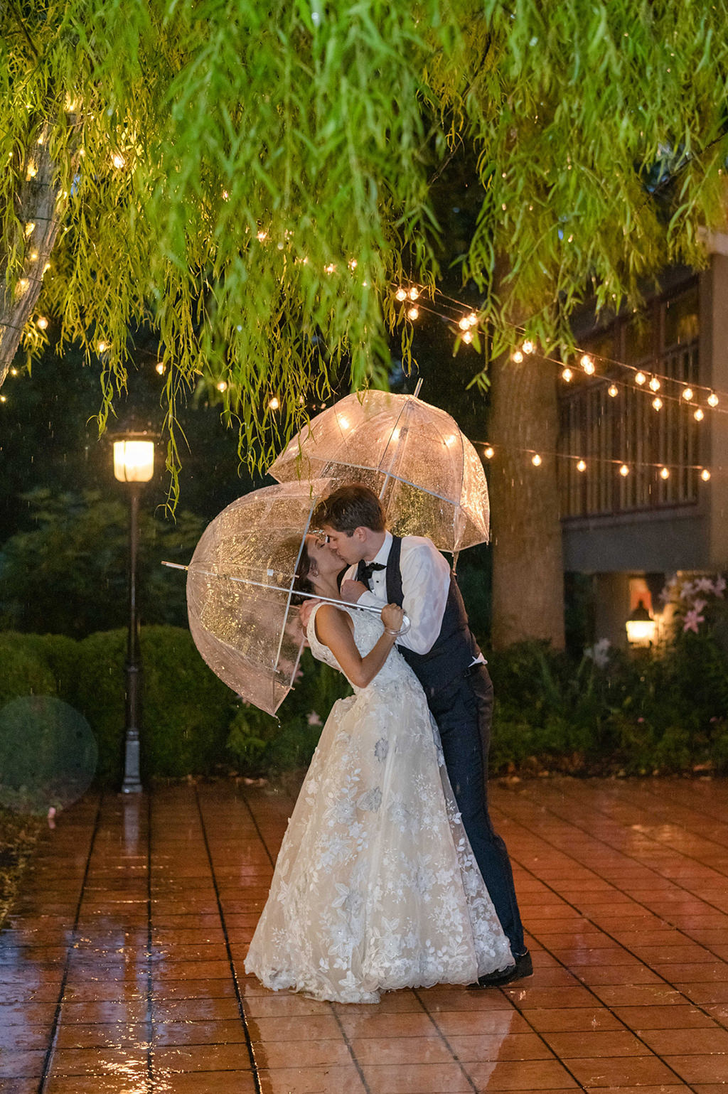 A bride and groom kissing under umbrellas in the rain. This was taken at their wedding at Moonstone Manor.