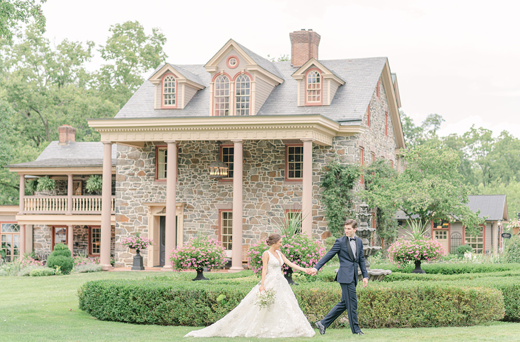 A bride and groom walking in front a Moonstone Manor, their PA wedding venue.