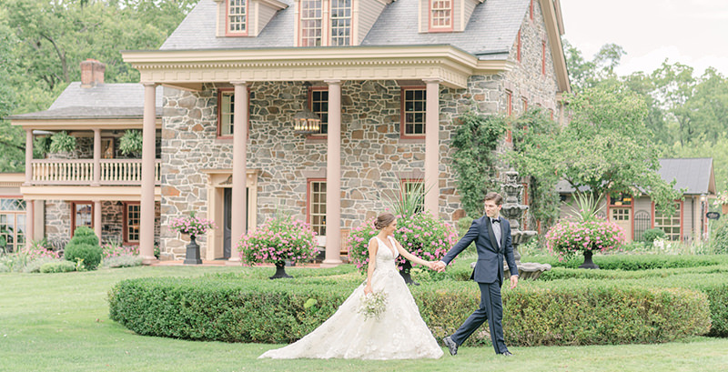 A bride and groom walking in front of Moonstone Manor after their wedding.