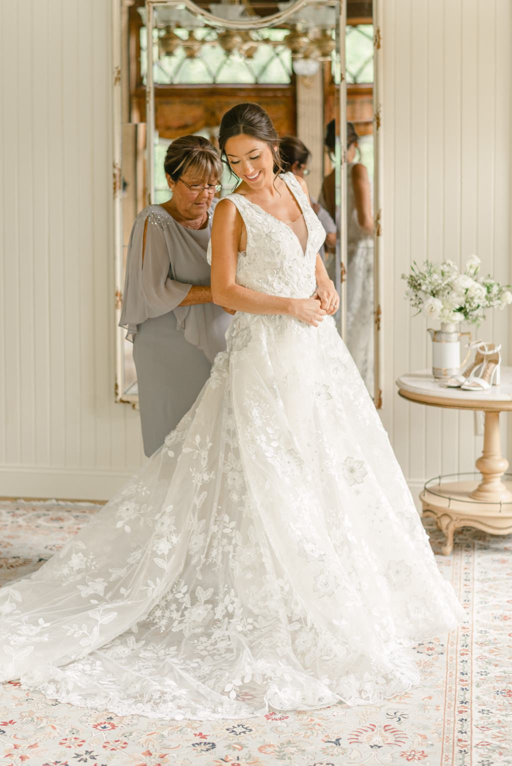 A mom helping the bride put on her wedding dress at Moonstone Manor.